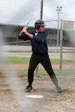 Batter Up. A teen boy up to bat with a unique view through the fence stock photo