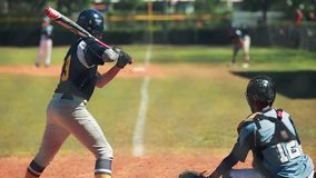 Batter waiting to bat during baseball game with catcher behind him stock video footage
