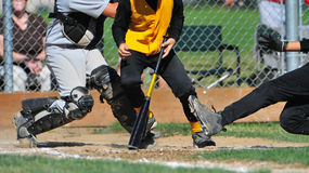 Batter in the way. A batter is caught between a runner sliding into home and the catcher stock photo