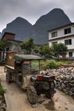Battered ancient farmer tractor stands in peasant village, Guang Stock Photography