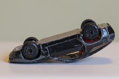 A battered black  toy car upside-down. Side view of a battered small black metal toy car upside down Royalty Free Stock Images