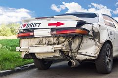 Battered drift car. Against the blue sky and green trees royalty free stock image