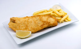 Battered fish and chips with lemon wedge and tartar sauce Royalty Free Stock Photos