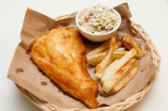 Battered fish and french fries. Fish and chips, a classic diner meal. This fresh haddock fillet is coated with batter and deep fried with home made french fries Royalty Free Stock Images