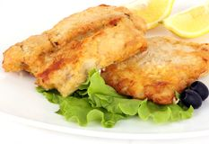 Battered fish. With olives and lemon on white Royalty Free Stock Image