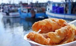 Battered fish served on a plate against fishing boats at sunset Stock Image