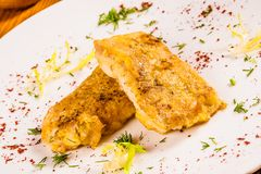 Battered fish with spices on white plate. Close up stock images