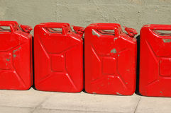 Battered fuel cans. Line of four red battered fuel cans against a wall Royalty Free Stock Photos