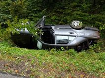 A battered gray car sedan lies in a roadside ditch among the lush green foliage of the bush in the summer. Road traffic incident. stock images