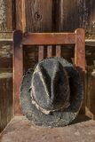 Battered old hat damaged by clothes moth on vintage background. Stock Images