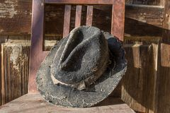 Battered old hat damaged by clothes moth on vintage background. Stock Photos