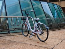 Battered Old Push Bike in Modern Stainless Steel Bike Rack. A solitary  battered old style white step through push bike or bicycle in a modern stainless steel stock photography