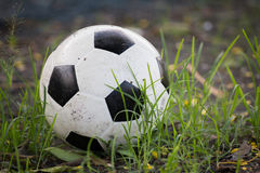 Battered old soccer ball, slightly deflated, in long grass of un Royalty Free Stock Image
