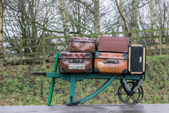 Battered old suitcases on a barrow at a railway station Royalty Free Stock Photos