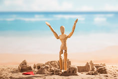 Battered sandcastles and wooden doll with hands up against sea. Stock Images