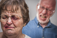 Battered and Scared Woman with Ominous Man Behind Stock Photography