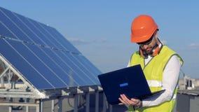 Batteria solare e un costruttore maschio che lavora con il suo computer portatile vicino Concetto di conservazione di potere di e stock footage