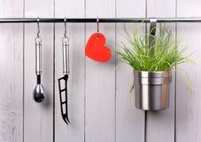 Batterie de cuisine rouge de coeur et de cuisine sur inoxydable Photographie stock libre de droits