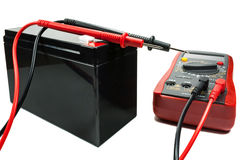 Batterie de secours avec un multimètre et sondes sur un fond blanc image stock