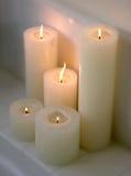 Batterie des bougies allumées sur une saillie Photographie stock libre de droits