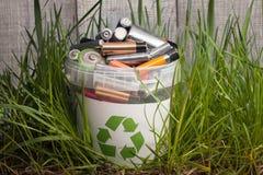 Batteriepapierkorb mit altem Element auf hölzerner Tabelle im Gras Lizenzfreies Stockbild