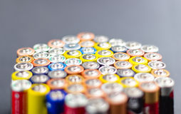 Batteries. Battery AA texture blurred in a row. Defocused rows of batteries, perspective view. Multicolored batteries AA, cell row hexagon organized Stock Image