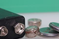 Batteries of corrosion of various shapes and sizes. They lie scattered on a white surface, on a green background. Environmental pr. Otection, recycling of used royalty free stock images