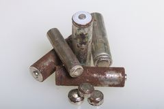 Batteries of corrosion of various shapes and sizes. Lies loose on a white background. Environmental protection, recycling of used. Batteries stock photography