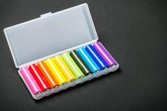 Batteries de différentes couleurs dans une boîte Photographie stock libre de droits