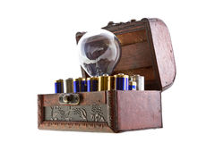 Batteries energy for an idea. Concept shot. Opened treasure chest with batteries and and a bulb lamp inside isolated on white stock photo