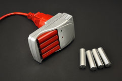Batteries recharging. Silver charger, red and  silvery battery on a black background Royalty Free Stock Images