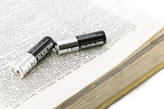 Batteries. Silver and black batteries on a dictionary opened at energy Royalty Free Stock Images