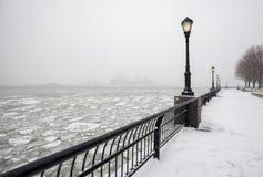 Batteriet parkerar under snö med djupfrysta Hudson River, New York Arkivbilder