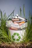Batterij kringloopbak met oud element op houten lijst in gras Stock Fotografie