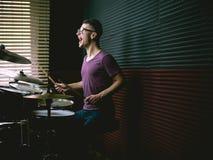 Batterista nello studio di musica che gioca i tamburi immagine stock