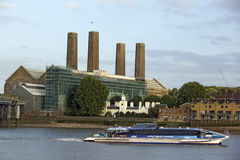 Battersea Power Station. The iconic Battersea power station as seen from the otherside of the Thames river with a thames taxi boat passing by. Picture is good to Stock Photos