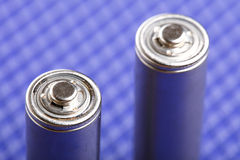 Battery on blue background Royalty Free Stock Photos