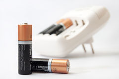 Battery charger and batteries on a white background Stock Images