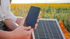 Battery charger solar powered outdoor, renewable energy, close up screen cellular telephone, hands girl connects from. Solar panel to mobile phone outside, cell stock video footage