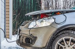 The battery of a dirty silver car is charged using a red charger plugged into an electrical outlet in winter. The battery of a dirty silver car is charged using stock images