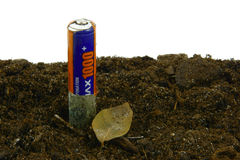 Battery. Environmental pollution. The old battarey decomposes in the ground Royalty Free Stock Photo