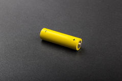 Battery. One yellow battery AA isolated on black or dark grey background. Diagonal composition of battery AA size Stock Image