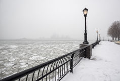 Battery Park under snow with frozen Hudson River, New York. Frozen Hudson River from snowy Battery Park towards Jersey City in fog. A silent winter day in New Stock Images