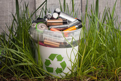 Battery recycle bin with old element on wood table in grass royalty free stock image