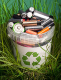 Battery recycle bin with old element on wood table in grass royalty free stock photo