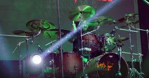 Batteur masculin à l'étape dans l'illumination colorée des lampes sur le concert de rock banque de vidéos