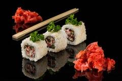 Batteurs blancs, bâtons en bois pour des sushi et gingembre sur l'acryle noir Images stock