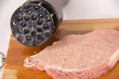 Battez la viande sur un conseil en bois sur un fond blanc Image stock