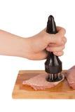 Battez la viande sur un conseil en bois sur un fond blanc Photos stock