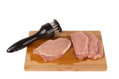 Battez la viande sur un conseil en bois sur un fond blanc Images libres de droits